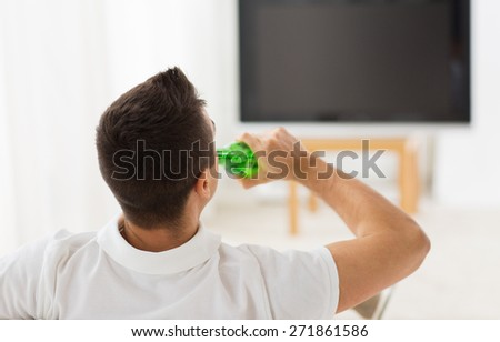 leisure, technology, mass media and people concept - man watching tv and drinking bottle beer at home from back - stock photo