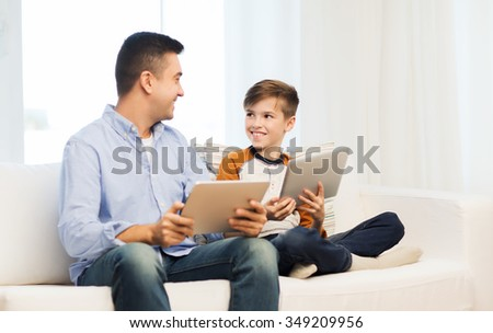 leisure, technology, technology, family and people concept - happy father and son with tablet pc computer networking or playing at home - stock photo