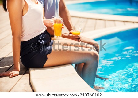 Leisure time poolside. Close-up of couple in casual wear sitting poolside together and drinking cocktails - stock photo
