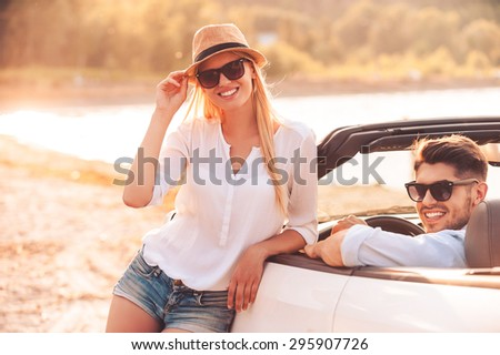 Leisure time we are spending together. Happy young woman leaning at white convertible while her boyfriend sitting on the front seat of it  - stock photo