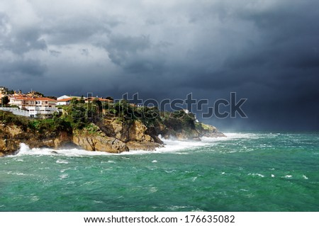 lekeitio coastline and cliffs with storm and rough sea - stock photo
