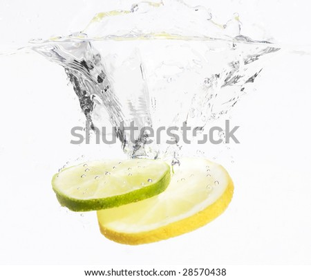 lemon and lime dropped with a splash into water - stock photo