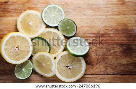 Lemon and limes on rustic wood - stock photo