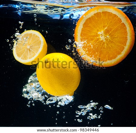 Lemon and orange floating in the water on a black background - stock photo