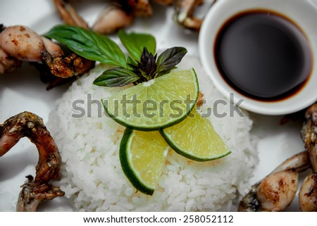 Lemon and rice on the white plate. Restaurant - stock photo