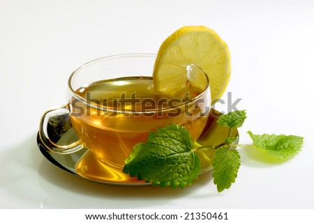 Lemon balm tea in a glass cup with garnish on light background