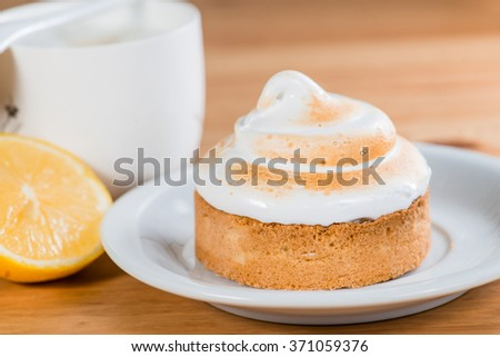 lemon cake on a saucer with a cappuccino on a wooden background (shallow DOF) - stock photo