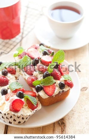 Lemon Cake topped with whipped cream, fresh fruits and mint - stock photo