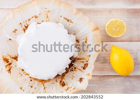 Lemon cake with white icing and fresh lemons - stock photo