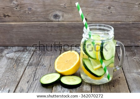 Lemon cucumber detox water in a mason jar glass with straw and slices against a rustic wood background