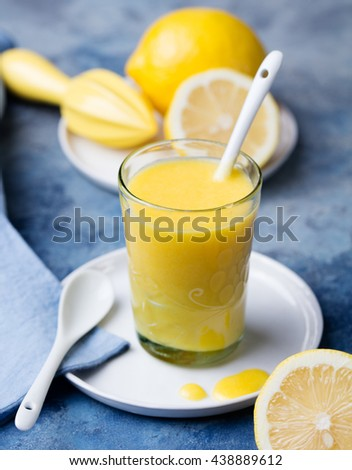 Lemon curd in glass with fresh lemons Blue stone background - stock photo
