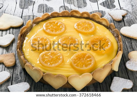 Lemon custard tart, decorated with biscuits in the form of hearts and lemon rings cooked in sugar syrup on an old wooden table - stock photo