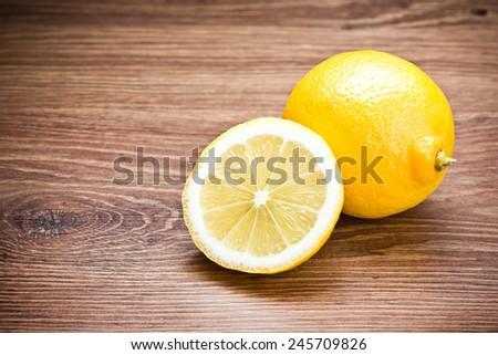 Lemon cut on wooden table. - stock photo