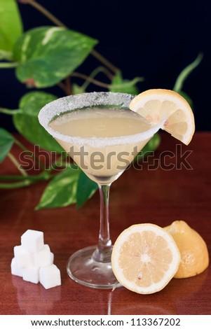 Lemon drop martini served on a bar top with fresh lemons and sugar cubes, garnish with a lemon slice and sugar rim - stock photo