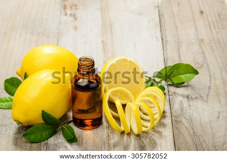 lemon essential oil and lemon fruit on the wooden board, (taken with tilt shift lens) - stock photo