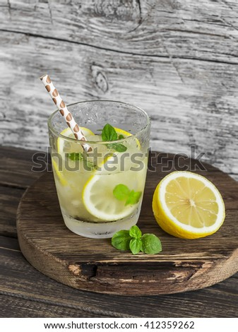 Lemon, ginger and mint lemonade on a wooden rustic board. Cold refreshing drink - stock photo