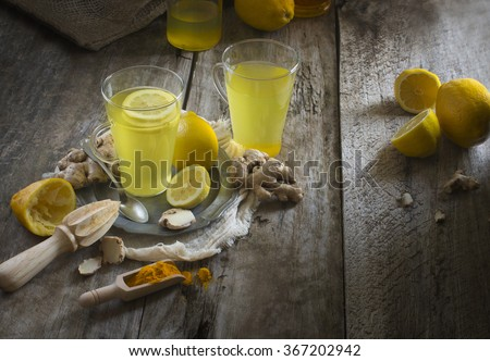 Lemon, ginger root and turmeric powder detox liver fat burnner healthy drinks on moody rustic wooden table top. Shallow depth of field blurry background. - stock photo