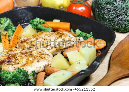 Lemon grilled chicken breast with fried vegetables in pan - stock photo