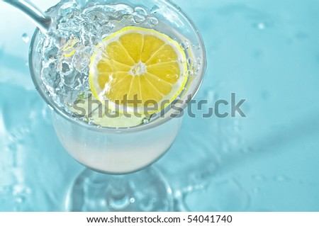 Lemon in glass water with bubbles - stock photo