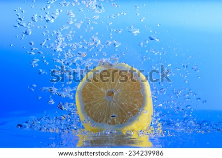 Lemon in water with bubbles. blue background - stock photo