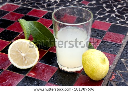 Lemon juice and lemon on a chess board - stock photo