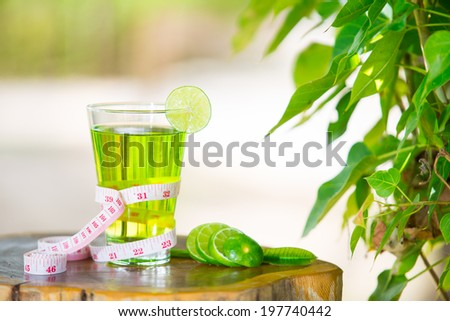 Lemon juice healthy fruit and tape measure placed on the table in the morning. - stock photo