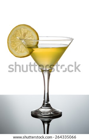lemon martini on reflective table with lemon slice
