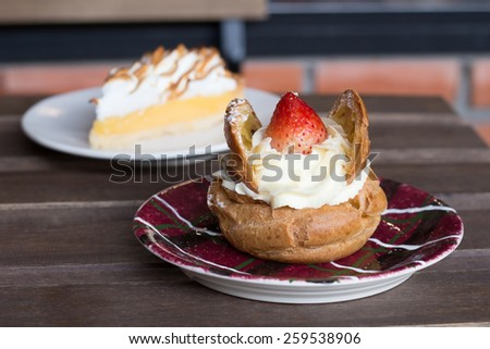 Lemon meringue pie and Cream puff strawberries - stock photo