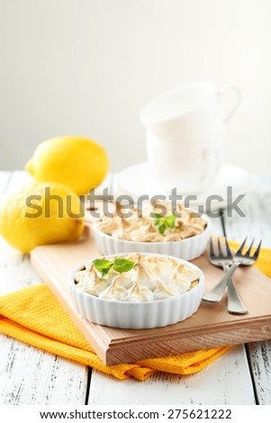 Lemon meringue pie in bowl on white wooden background - stock photo