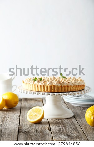 Lemon meringue pie on cake stand on grey wooden background - stock photo