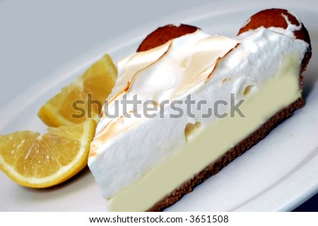 Lemon meringue pie with lemons in background. - stock photo
