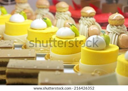 Lemon mousse cake canapes in the cake shelf - stock photo