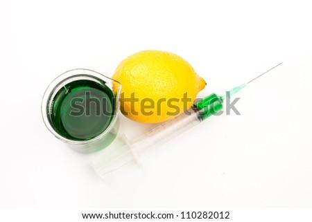 Lemon next to beaker and a syringe against a white background - stock photo