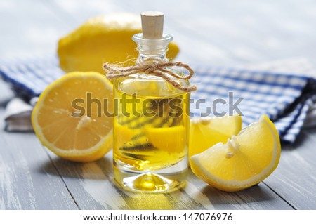 lemon oil in a glass bottle with fresh ���«���¥���¬���®���­ ���®���­ wooden background - stock photo
