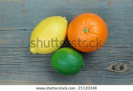 Lemon, orange and lime on distressed old barn wood plank - stock photo