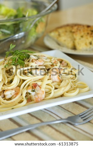 Lemon Pepper Shrimp Linguine Served with Salad and Garlic Parmesan Toast - stock photo