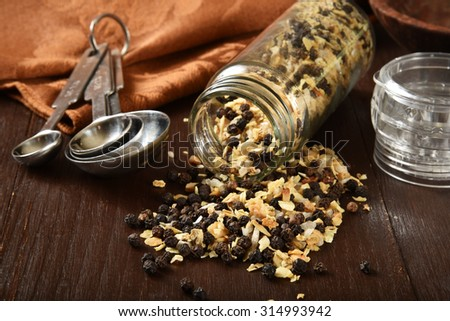 Lemon pepper spilling out of a spice jar, shallow depth of field - stock photo