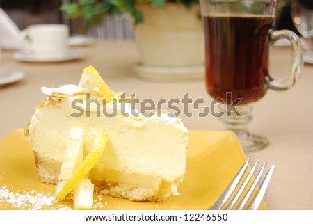 Lemon pie on a yellow plate with coffee in the background on a restaurant table. - stock photo