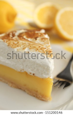 Lemon pie with meringue and a fork in a plate - stock photo
