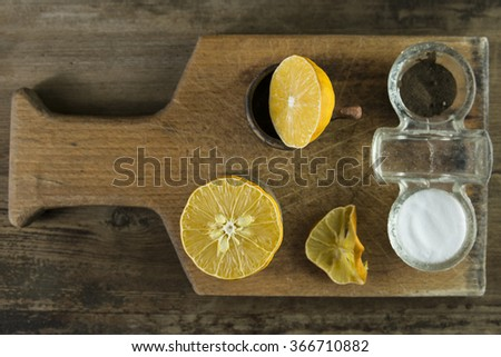 Lemon, salt and pepper on cutting board - stock photo