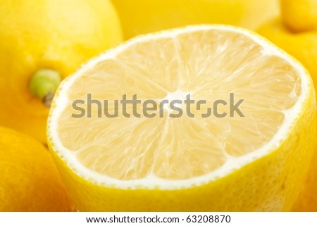 Lemon slice closeup. Background are other lemons.