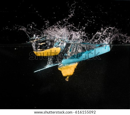 Lemon sliced with blue knife falling into the water on the black background.