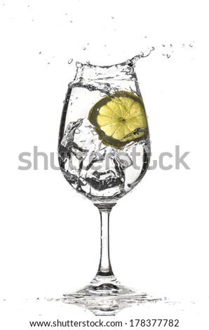 Lemon splash in water glass - stock photo