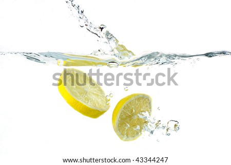 Lemon splashing into water; white background - stock photo