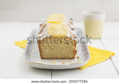 Lemon sponge cake with candied lemon slices and icing on top - stock photo