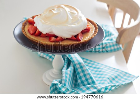Lemon strawberry meringue pie on a cake stand - stock photo