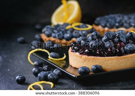 Lemon Tart and tartlets with fresh and cooked blueberries, served on black square plate with lemon and lemon zest over black background. - stock photo