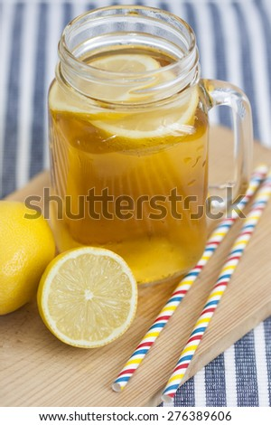 Lemon tea  in a mason jar with straws. - stock photo