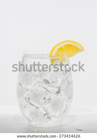 Lemon wedge sitting on lip of glass of water with ice cubes.