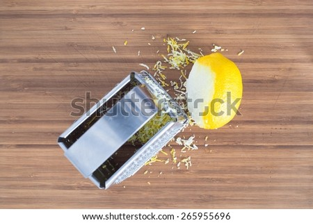 Lemon zesting with metal grater, top view - stock photo